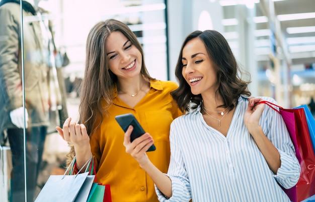 Lindas amigas felizes e animadas com sacos de papel e um telefone inteligente andando pelo shopping