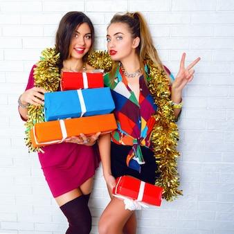 Lindas amigas felizes e sorridentes segurando presentes e presentes para festas. vestindo roupas da moda e enfeites dourados