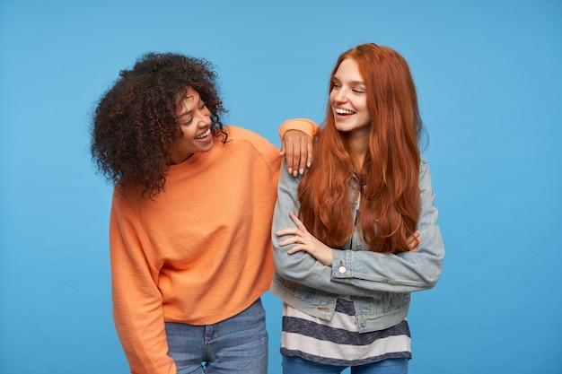 Lindas amigas felizes olhando alegremente uma para a outra e sorrindo alegremente, estando em alto astral enquanto ficam de pé sobre uma parede azul em roupas casuais