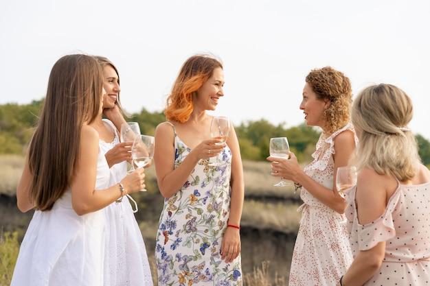 Lindas amigas se divertindo, bebendo vinho e aproveitando o piquenique nas montanhas