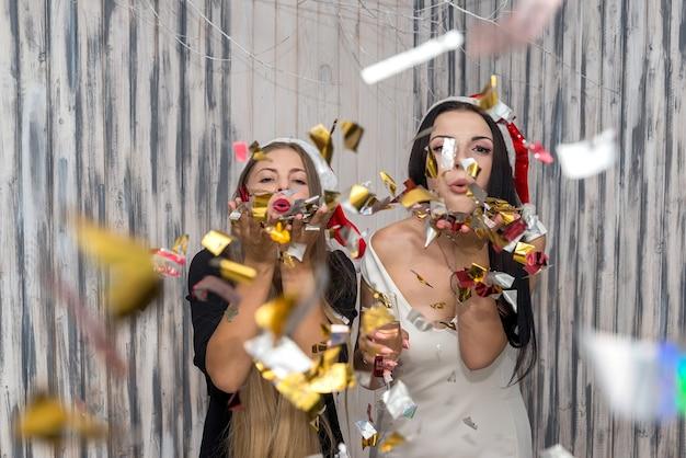 Lindas amigas soprando confetes brilhantes no estúdio