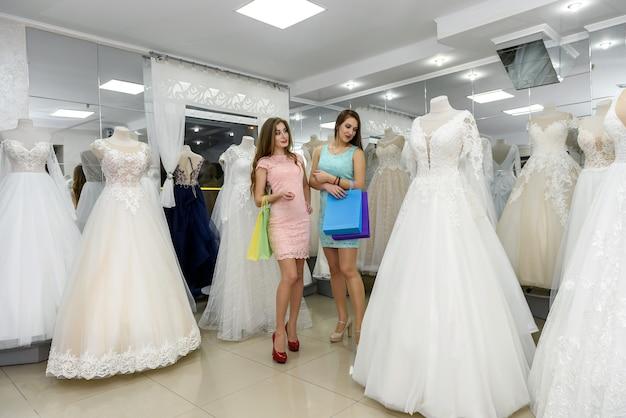 Lindas amigas sorridentes escolhendo um vestido de noiva na loja