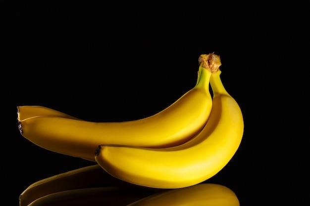Lindas bananas maduras em fundo preto, conceito de comida saudável