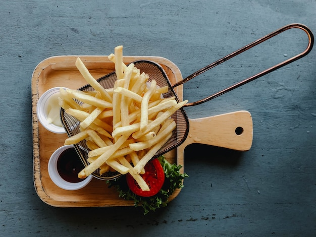 Lindas batatas fritas em uma mesa de madeira