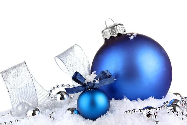 Lindas bolas de natal azuis na neve, isoladas no branco