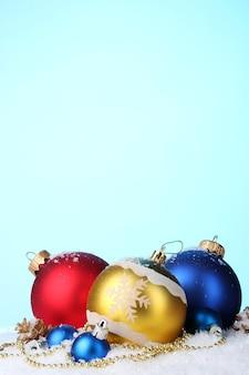 Lindas bolas de natal brilhantes e cones na neve no azul