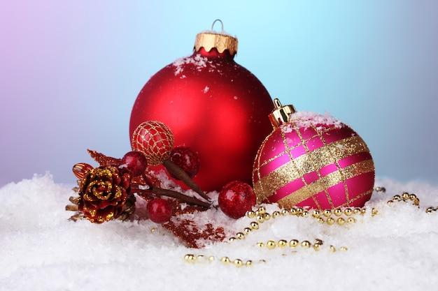Lindas bolas de natal e cone na neve no fundo brilhante
