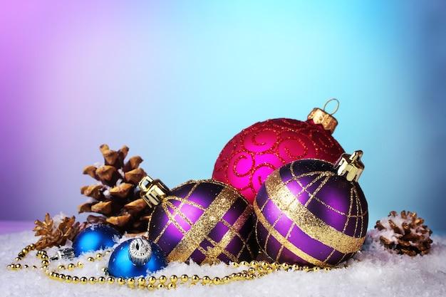Lindas bolas de natal e cones na neve no fundo brilhante