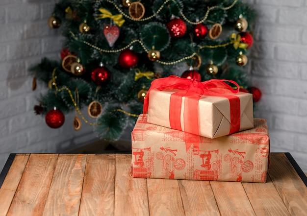Lindas caixas de presente de natal na mesa de madeira ao lado da árvore de natal na sala