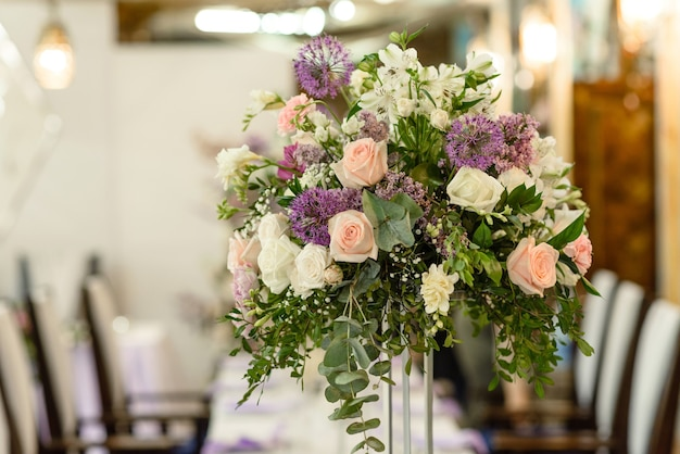 Lindas composições florais no restaurante para a cerimônia de casamento. cerimônia solene de pintura do noivo e da noiva