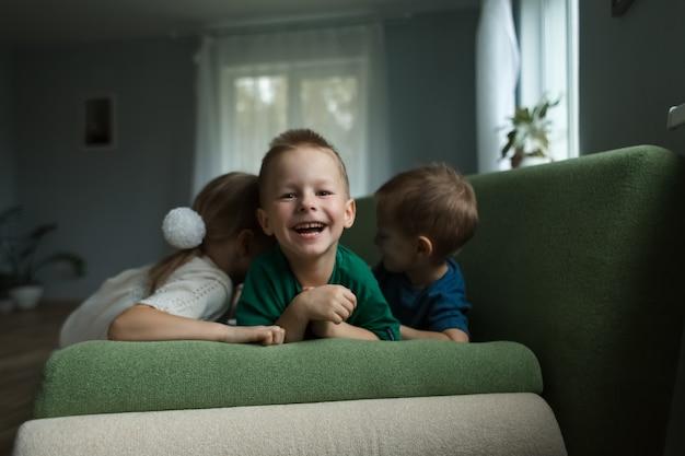 Lindas crianças deitadas no sofá rindo em casa. o menino está olhando para o meio.