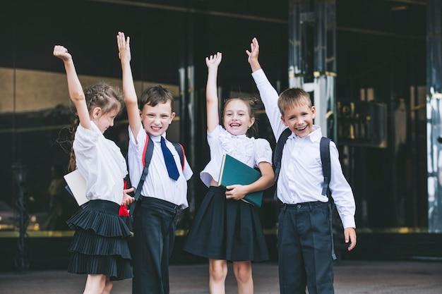 Lindas crianças em idade escolar, ativas e felizes no fundo da escola, de uniforme