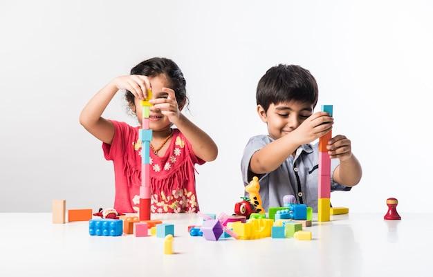 Lindas crianças indianas asiáticas brincando com brinquedos de plástico coloridos ou blocos enquanto estão sentadas à mesa ou isoladas sobre um fundo branco