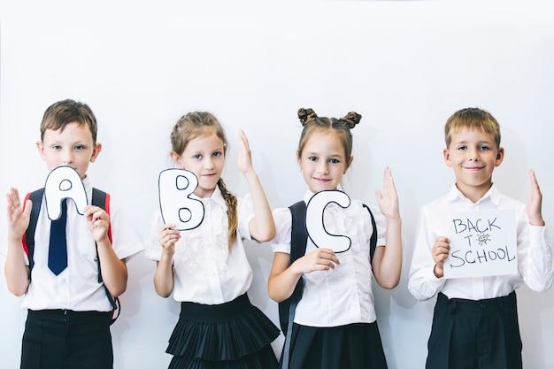 Lindas crianças são alunos juntos em uma classe na escola. as placas de fundo branco estão recebendo educação felizes