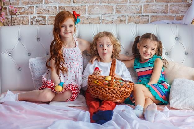 Lindas crianças sentam juntos em uma cama com ovos de páscoa em suas mãos e se divertir.