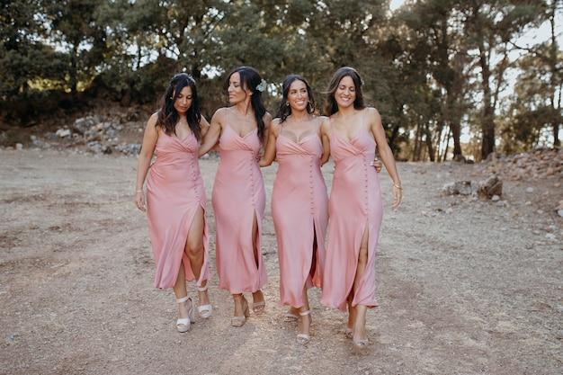 Lindas damas de honra em lindos vestidos ao ar livre