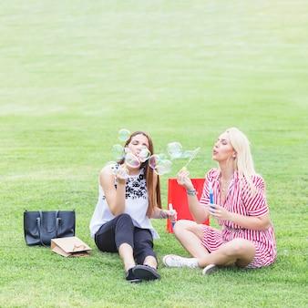 Lindas duas amigas sentado na grama verde, soprando bolhas