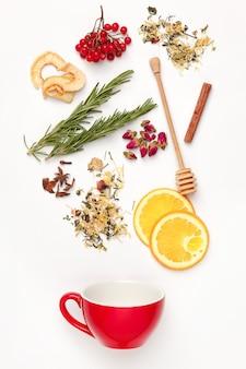 Lindas e deliciosas folhas secas de chá com ervas, flores, frutas vermelhas, frutas caindo na xícara de chá sobre fundo branco