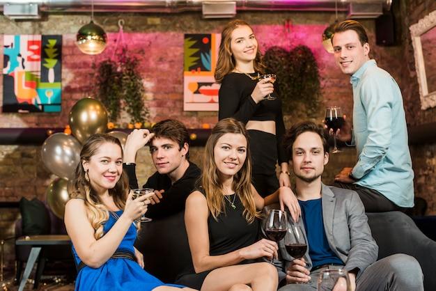 Lindas felizes jovens casais apreciando a bebida na festa