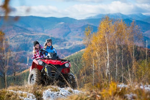 Lindas fêmeas andando na moto quad vermelho nas montanhas nevadas