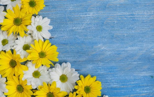 Lindas flores amarelas e brancas em uma mesa de madeira