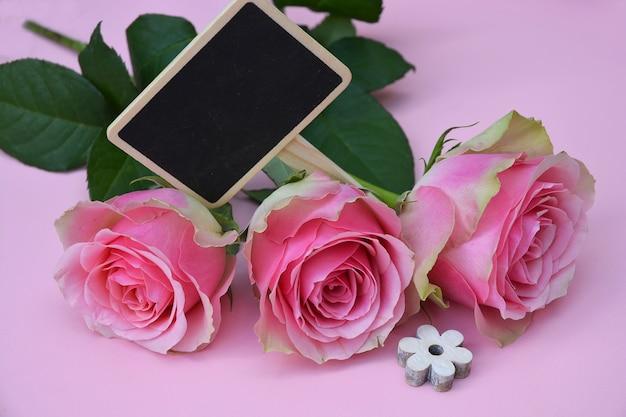 Lindas flores cor de rosa com uma flor em forma de madeira em uma superfície rosa