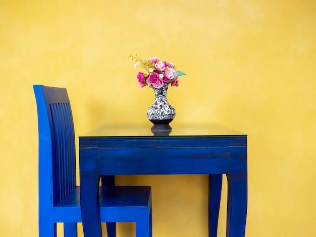 Lindas flores cor de rosa em um vaso de cerâmica vintage na mesa pintada de azul vívido e uma cadeira na parede amarela.