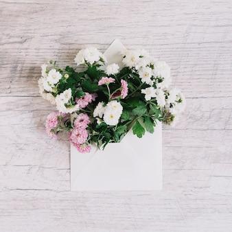 Lindas flores de áster-de-rosa e branco no envelope em plano de fundo texturizado de madeira