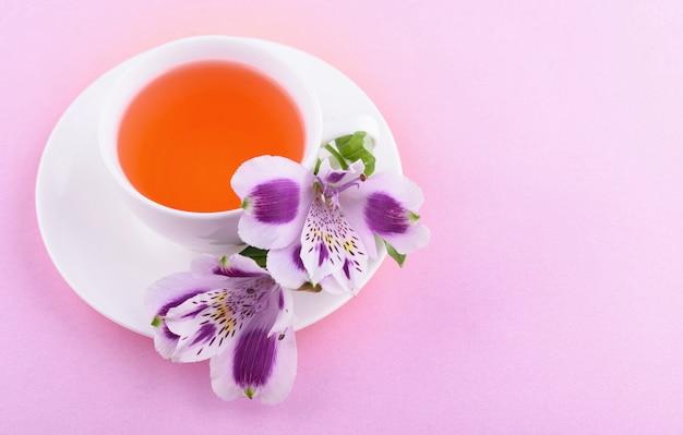 Lindas flores de astromeria. chá de ervas em uma xícara branca e um pires branco em um rosa