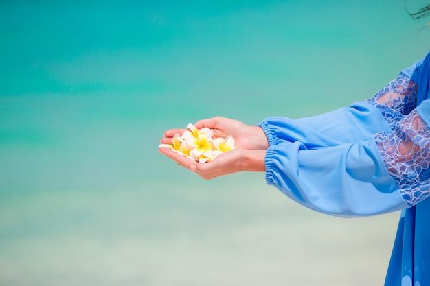 Lindas flores de frangipani em mãos femininas fundo mar azul-turquesa na praia branca