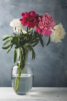 Lindas flores de peônia branca, roxa e rosa em um vaso de vidro.