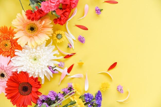 Lindas flores decoram na vista superior de fundo amarelo