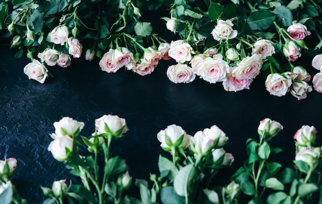 Lindas flores em fundo preto. buquê de rosas. colocação plana perfeita. cartão postal de férias da mãe feliz. saudação do dia internacional da mulher. ideia elegante para anúncio ou promoção.
