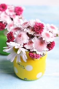 Lindas flores em latas na mesa na superfície clara