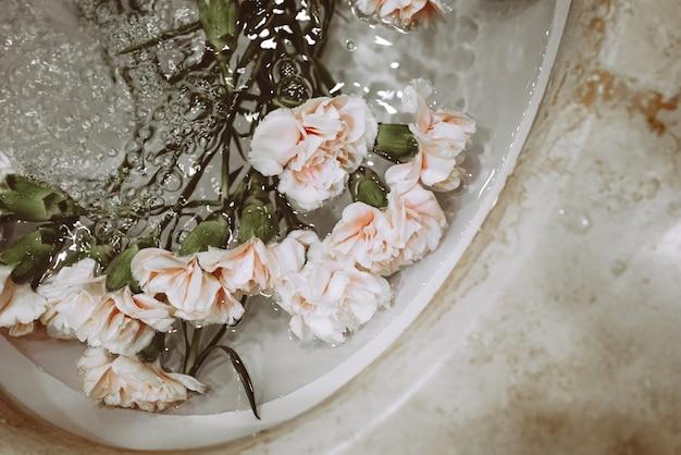 Lindas flores em uma pia com água. beleza estética