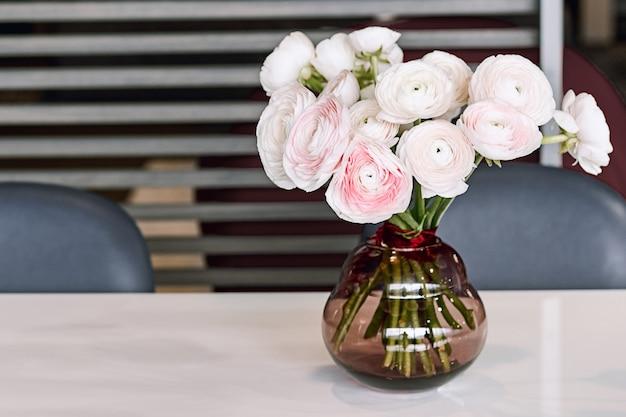 Lindas flores em vaso de vidro. ramalhete bonito do botão de ouro persa cor-de-rosa.
