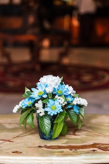 Lindas flores em vaso na mesa de madeira
