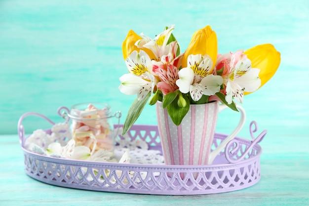 Lindas flores na taça na mesa de madeira colorida