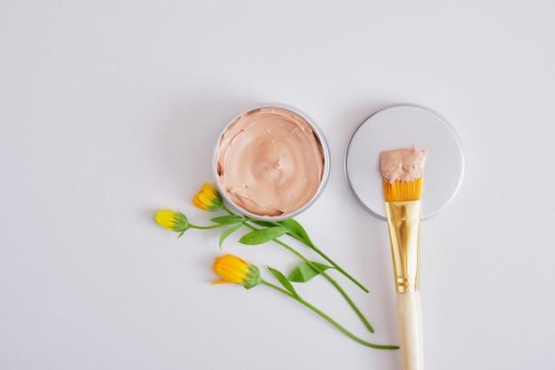 Lindas flores pequenas, pincel de maquiagem e argila vermelha cosmética em uma jarra de alumínio, cosméticos naturais