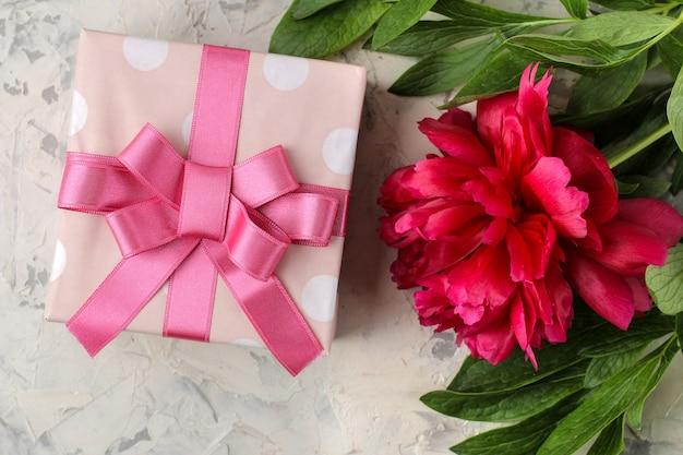 Lindas flores rosa brilhantes de peônias e uma caixa de presente em um fundo brilhante de concreto. vista do topo.