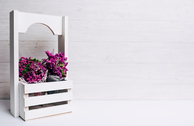 Lindas flores roxas minúsculas em caixas na mesa contra o pano de fundo de madeira