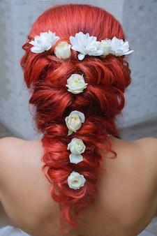 Lindas flores tecidas em sua garota de cabelo