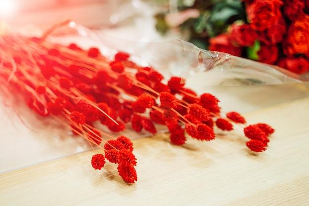 Lindas flores vermelhas frescas, deitado sobre a mesa de madeira clara perto das rosas vermelhas.