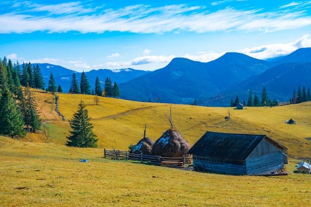 Lindas florestas coloridas cobrindo as montanhas dos cárpatos e uma pequena vila contra o fundo de um céu quente de outono