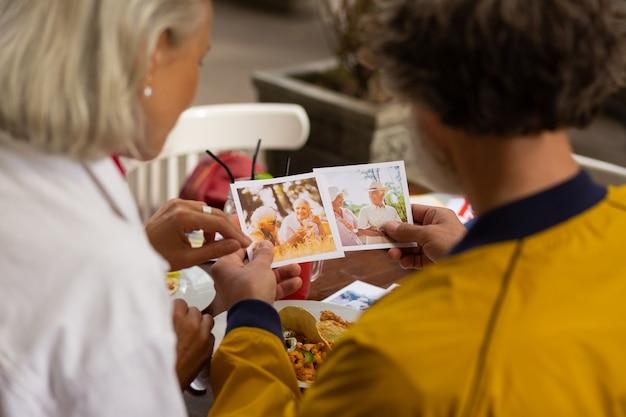 Lindas fotos. feliz marido e mulher sentados no café na hora do almoço, olhando as fotos de seus amigos.