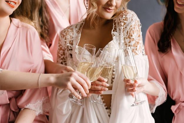 Lindas garotas, a noiva e seus amigos derramam champanhe em taças. dia mais feliz. foco seletivo