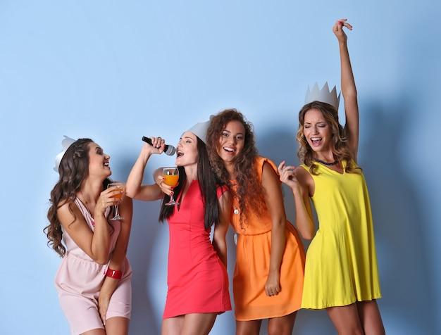 Lindas garotas com microfone no fundo da parede azul