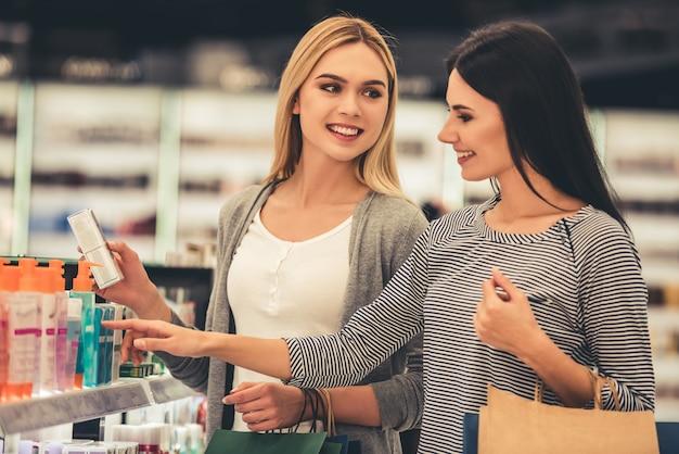 Lindas garotas com sacolas de compras estão escolhendo cosméticos.