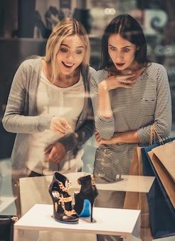 Lindas garotas com sacolas de compras estão escolhendo sapatos.