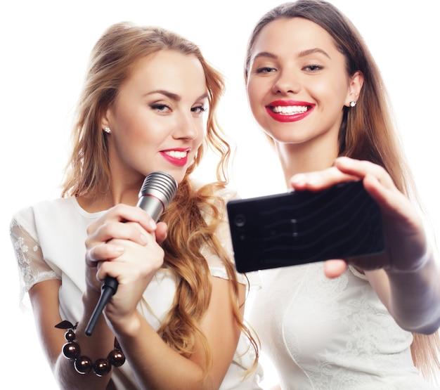 Lindas garotas com um microfone cantando e tirando selfie